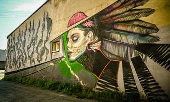 Mural na ścianie budynku przedstawiającą twarz kobiety.