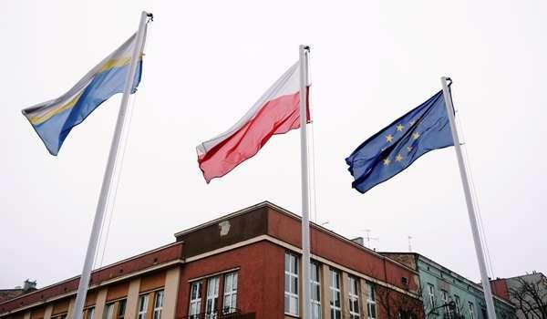 Flaga miasta, polski oraz unijna powiewające na wietrze